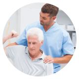 caregiver assisting an old man doing motor exercise